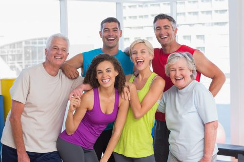 Cheerful people in sportswear at fitness gym